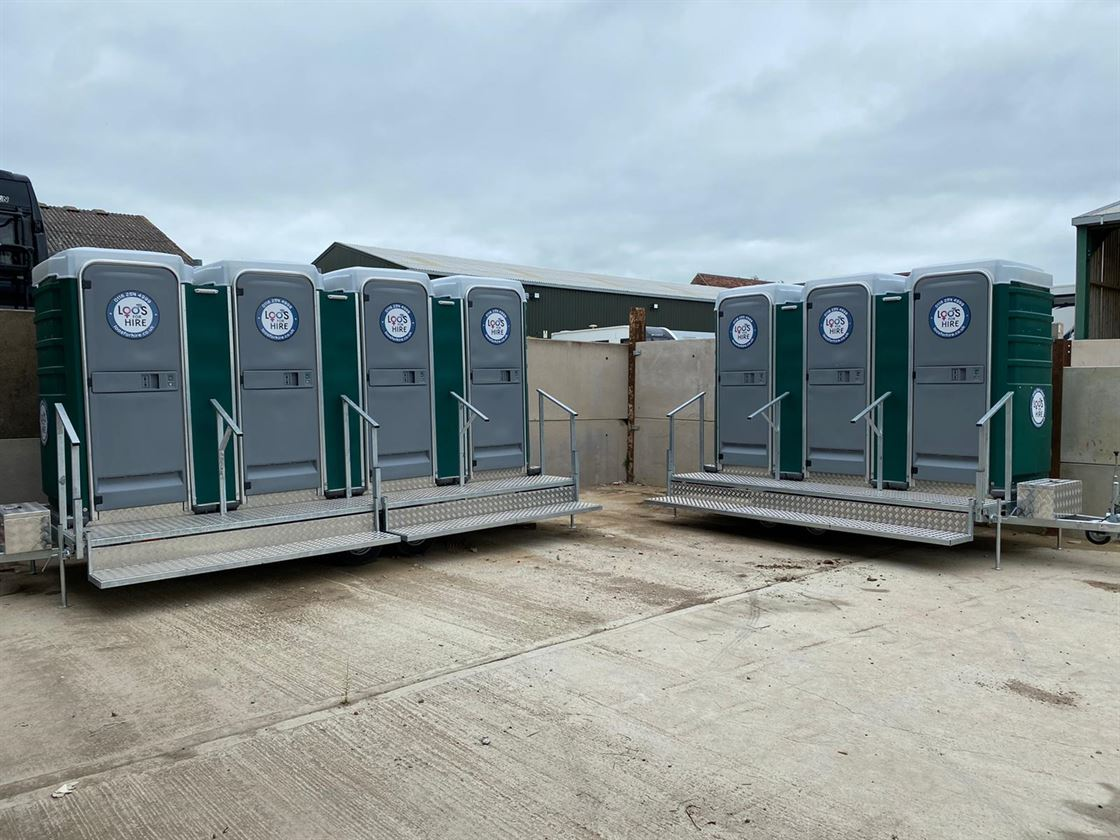 6 premium quality portable toilets in situ at an outdoor event.